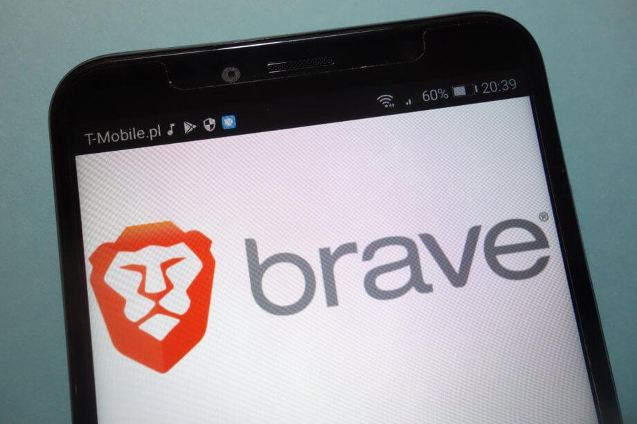 Ein Smartphone Display und im Hintergrund wird der Brave Browser angezeigt