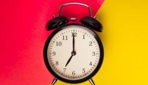 Ein Wecker der auf punkt sieben Uhr das Hintergrundbild ist zweigeteilt eine Seite ist rot und die andere Seite ist gelb
