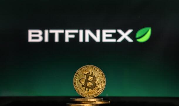 In der Mitte steht eine goldene Bitcoin Münze und im Hintergrund wird die Bitfinex Börse angezeigt