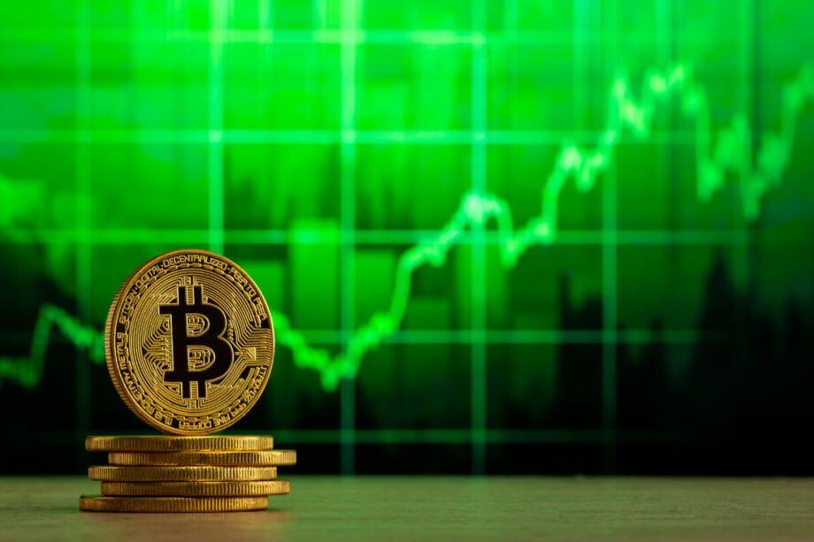 Mehrere goldene Bitcoin Münzen die gestapelt sind und im Hintergrund wird eine grüne Chart Linie angezeigt