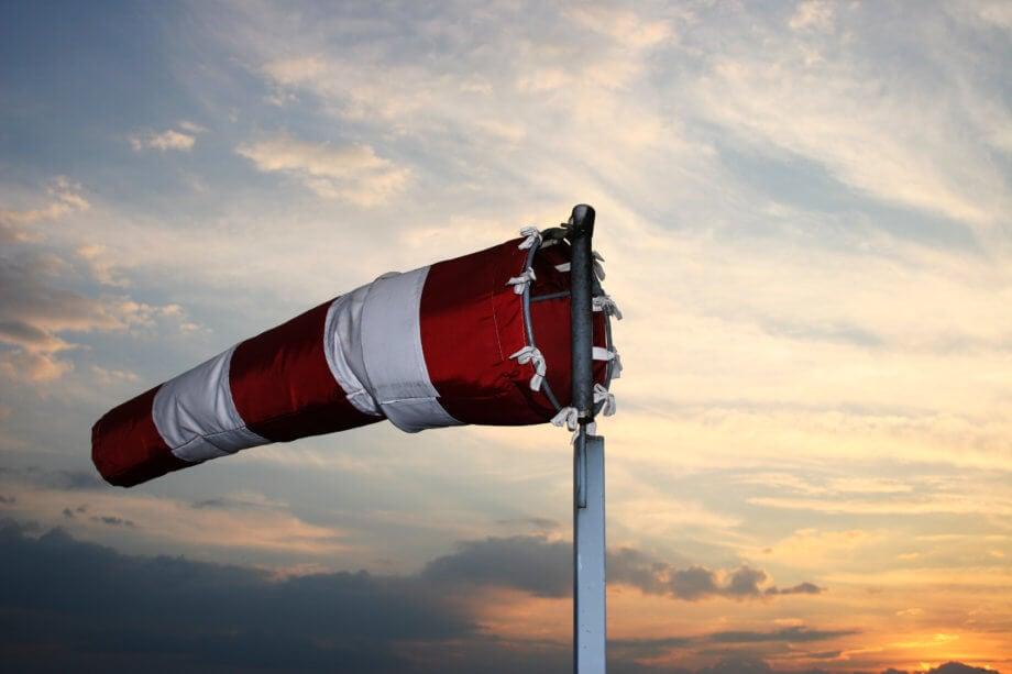 Windsack in den Farben Rot und Weiß dreht sich zum Wind im Hintergrund geht die Sonne unter