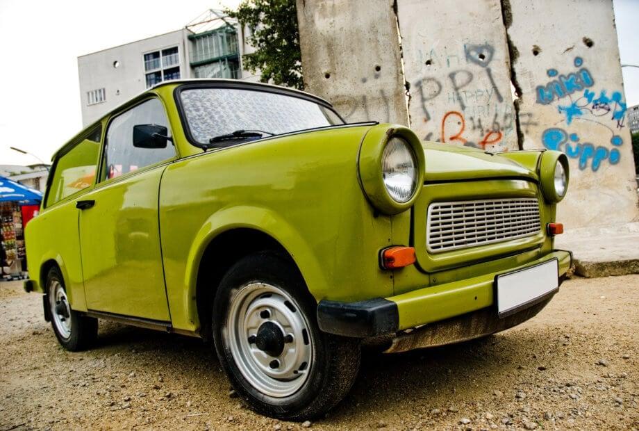 Grüner Trabant steht symbolisch für Digitaler Euro vor Graffiti Wand