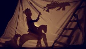 Schattenspiel ein Ritter auf seinem Pferd bekämpft einen Drachen mit seinem Schwert
