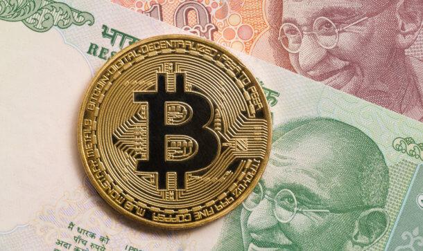 Goldene Bitcoin Münze liegt auf indischen Geldscheinen