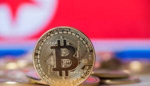 Eine balancierende Bitcoin-Münze vor einer Nordkorea-Flagge