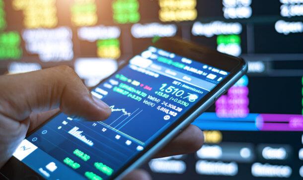smartphone mit daumen zeigt charts im hintergrund börse