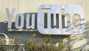 silbernes youtube symbol vor beigenem gebäude von der sonne geküsst von ripple verklagt