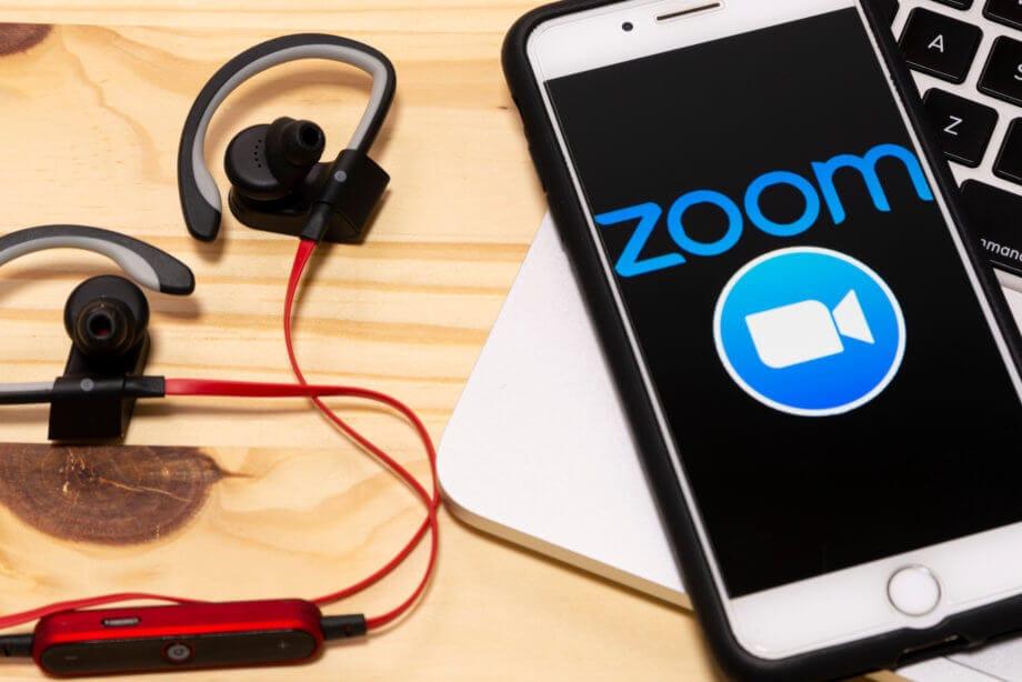 smartphone, auf dem das zoom-logo erkennbar ist, liegt neben kopfhörern auf einem holztisch