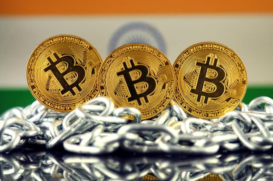 Drei Bitcoin-Münzen auf einer Kette, im Hintergrund die indische Flagge
