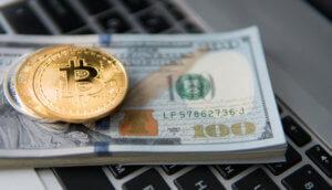Ein paar Bitcoin-Münzen auf einem Haufen Dollar-Scheine auf einem Laptop.