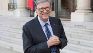 bill gates steht im anzug mit blau schwarzer krawatte und grauem haar vor einem gebäude, von dem man die treppenstufen sieht und lächelt