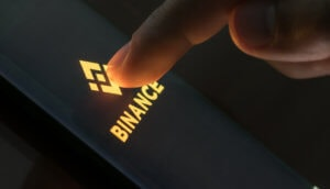 finger drückt auf smartphone mit binance-logo