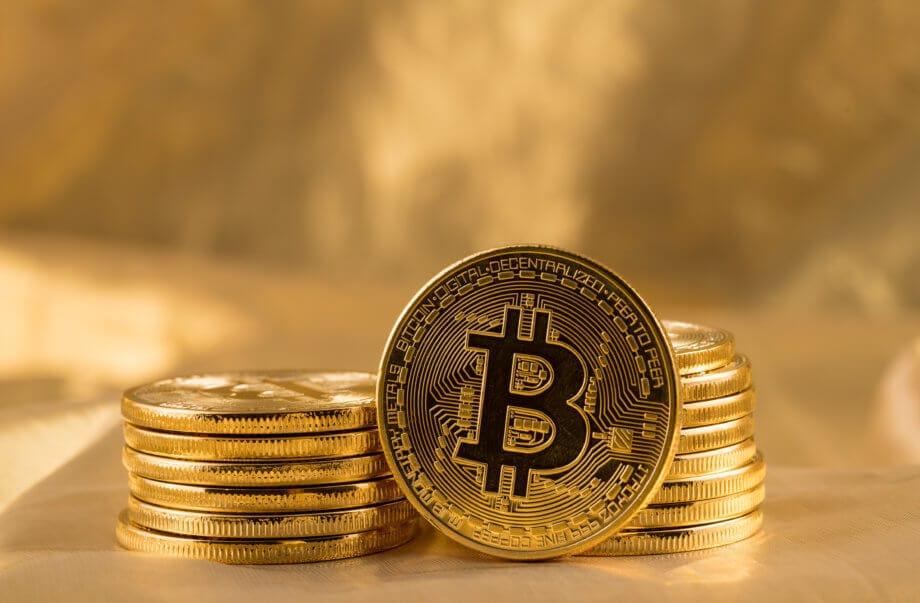 bitcoin-münze steht vor zwei stapeln mit bitcoin-münzen vor einem goldenen hintergrund