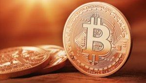 bitcoin-münze-steht-aufrecht-neben-liegenden-bitcoin-münzen-auf-einem-tisch