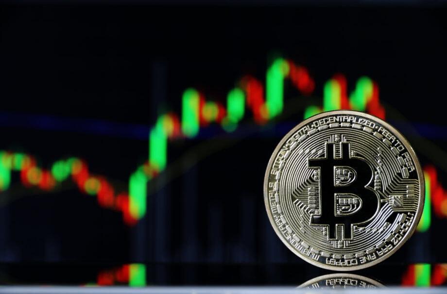 bitcoin-münze-steht-vor-einer-chart-mit-grünen-und-roten-kerzen