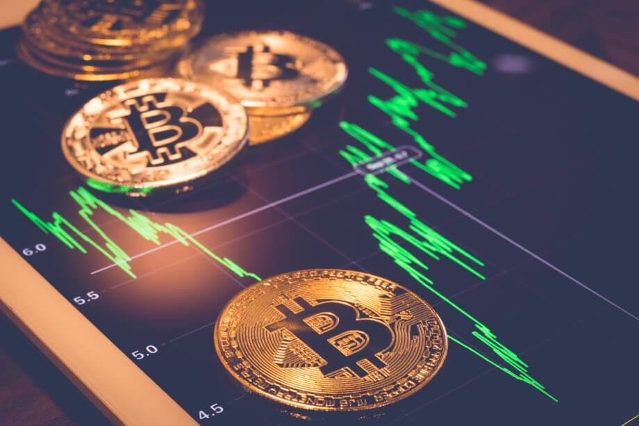 bitcoin münzen und der bitcoin-kurs auf einem tablett