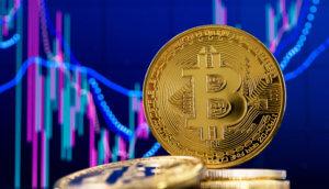 bitcoin-münze hinter liegenden bitcoin-münzen vor einer chart mit blauem hintergrund