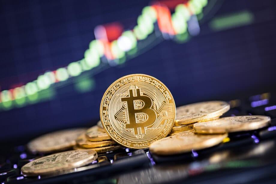 bitcoin-münze steht vor liegenden bitcoin-münzen vor einer chart