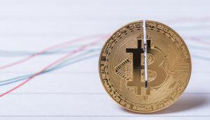 symbolische darstellung vom bitcoin halving in form einer halbierten bitcoin-münze auf einer chart