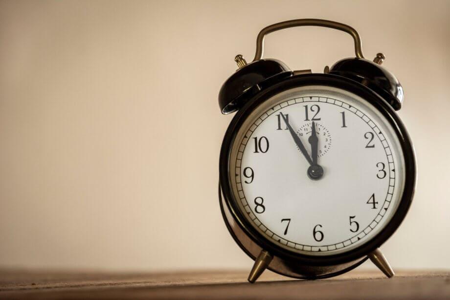 Altmodischer Wecker, die Uhrzeit steht auf fünf vor Zwölf.