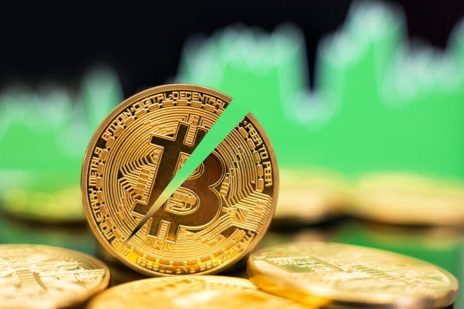 halbierte bitcoin münze die zwischen liegenden bitcoin münzen steht, im Hintergrund grüne Charts als Symbol für einen Bitcoin-Kurs-Anstieg nach dem Halving