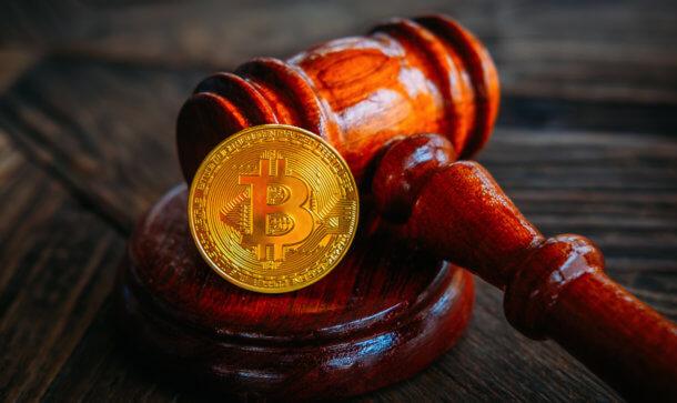 eine bitcoin münze die mit einem richter-hammer auf dem tisch liegt