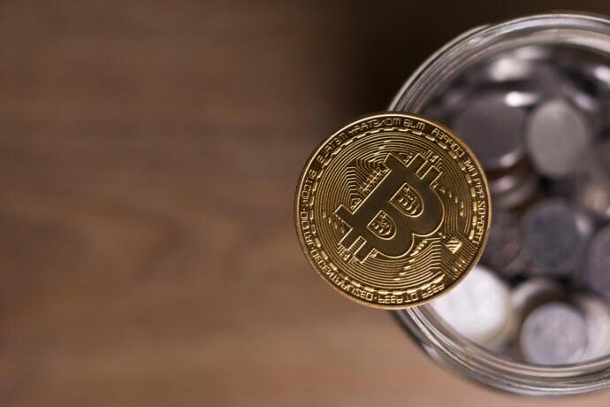 Bitcoin-Münze auf einem glas voller coins