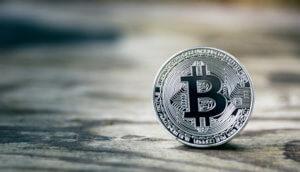 silberne bitcoin muenze auf einem tisch