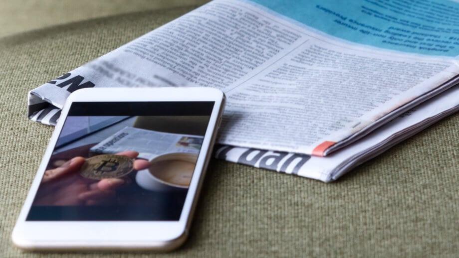 ein smartphone auf dem eine bitcoin münze und eine tasse kaffe gezeigt wird liegt auf einem tisch bei einer zeitung