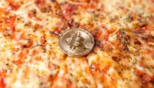 eine bitcoin münze auf einer pizza margaritha