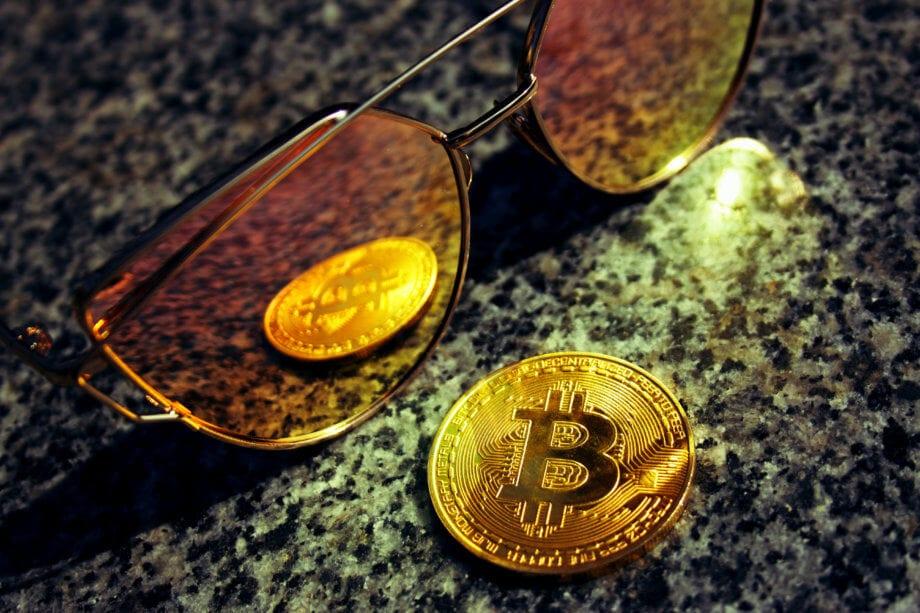 eine bitcoin-münze, die sich in einer sonnenbrille spiegelt