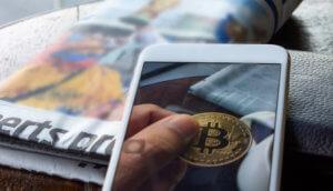 Bitcoin auf Iphone mit Tageszeitung daneben