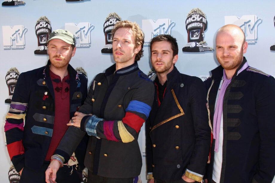 Die Bandmitglieder von Coldplay stehen vor einer Plakatwand für Fotoshooting.