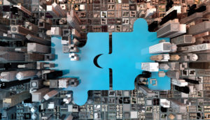 zwei blaue puzzleteile inmitten einer darstellung einer stadt mit hochhäusern