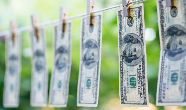 gewaschene dollarscheine hängen an einer wäscheleine zum trocknen und sind mit wäscheklammern befestigt worden als symbol für bitcoin geldwäsche