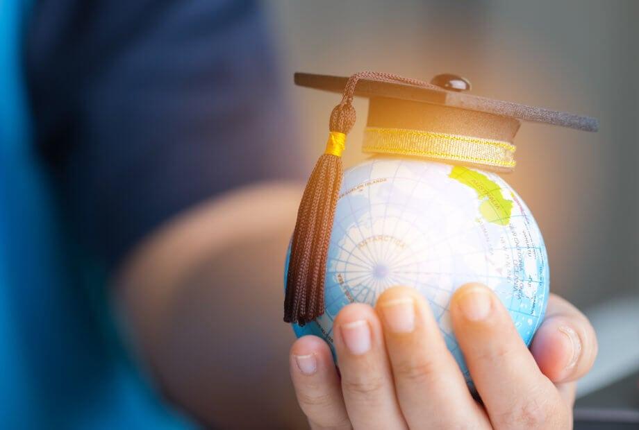 Frauenhand hält kleinen Globus mit Doktormütze