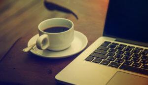 eine tasse kaffe steht auf einem tisch neben einem laptop als symbol für news im bereich bitcoin