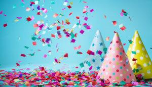 Konfetti wirbelt durch die Luft und man sieht Party-Zylinder, die das erfolgreiche Bitcoin Halving symbolisieren sollen.