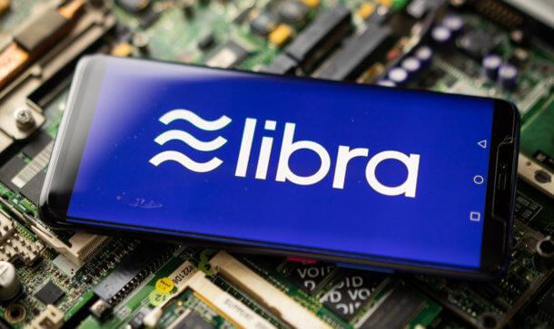 das libra-symbol auf einem smartphone, das auf einem elektronischen technologie-hintergrund liegt