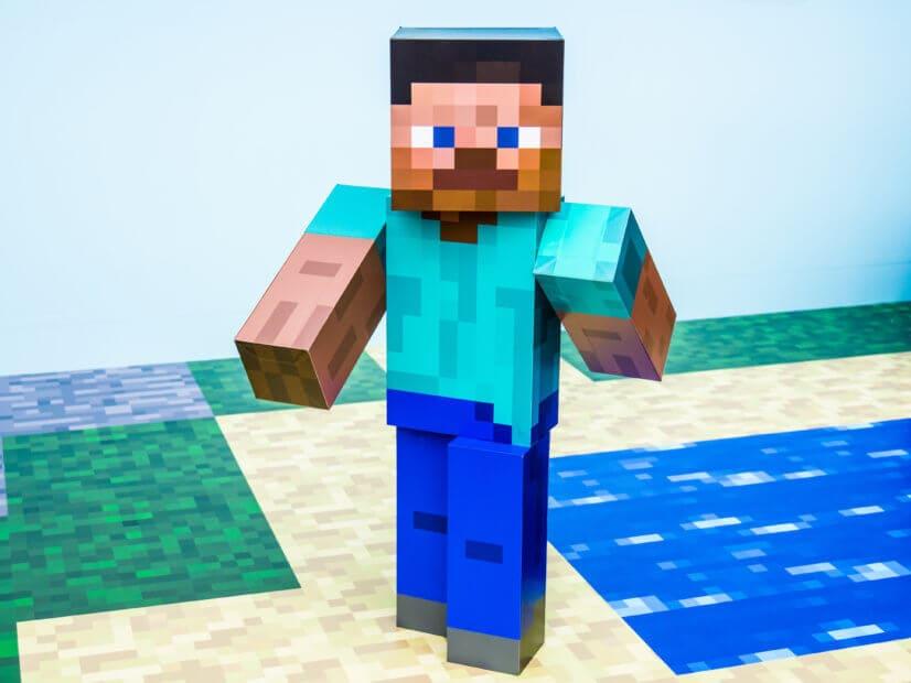 Eine Figur im Minecraft-Stil die an einem Stück Wasser vorbeiläuft