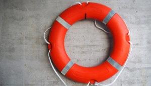 Ein roter Rettungsring auf grauer Wand