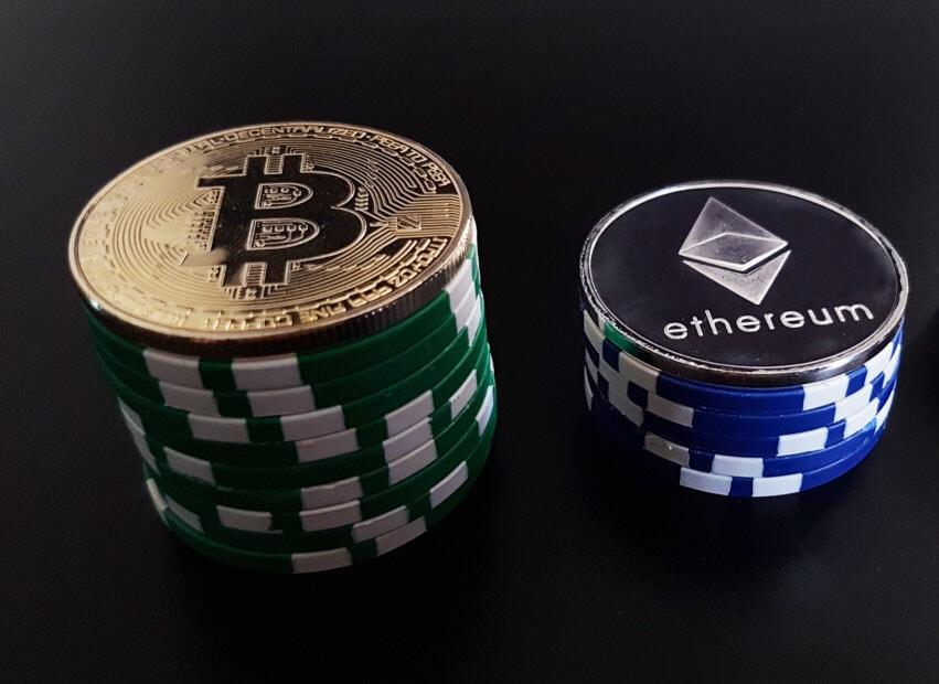 Zwei Stapel mit Pokerchips, links von Bitcoin, rechts von Ethereum-Münze gekrönt