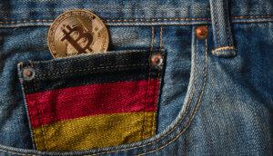 Bitcoin-Münze in schwarz-rot-gold-gefärbter Uhrentasche einer Jeans