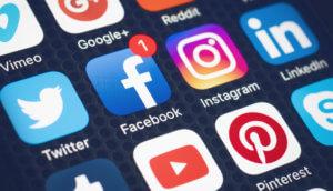 Ein Bildschirm, auf dem verschiedene Social Media Symbole angezeigt werden, darunter vimeo google plus reddit twitter facebook instagram linked in tumblr youtube pinterest und skype, ansicht von schräg oben, in der mittleren reihe befinden sich zentral twitter facebook instagram und linked in, bei facebook ist eine weiße eins in einem roten kreis
