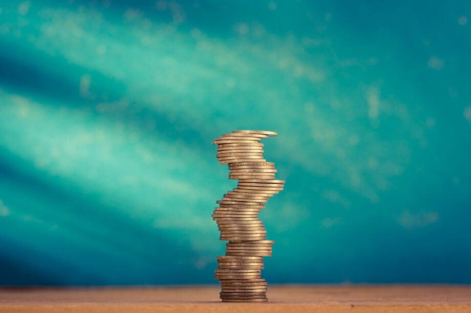 münzen, die aufeinander gestapelt sind und auf einem tisch stehen vor einem türkisenen hintergrund