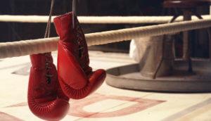 Ein Paar Boxhandschuhe hängt auf den Seilen eines Boxrings