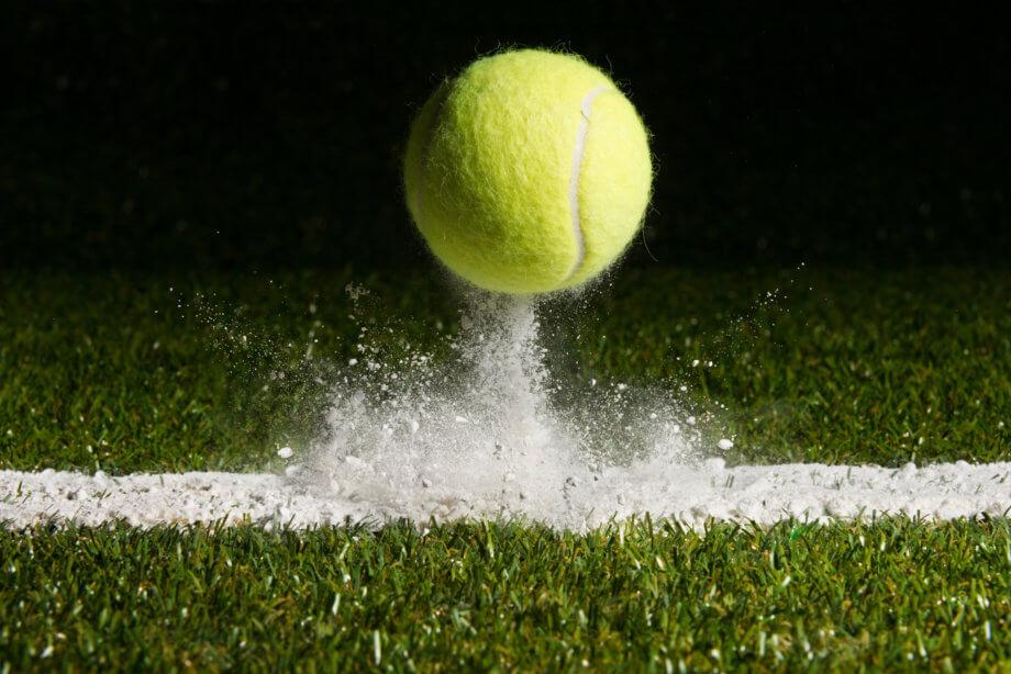 Tennisball prallt von weißer Linie auf grünem Rasen ab.