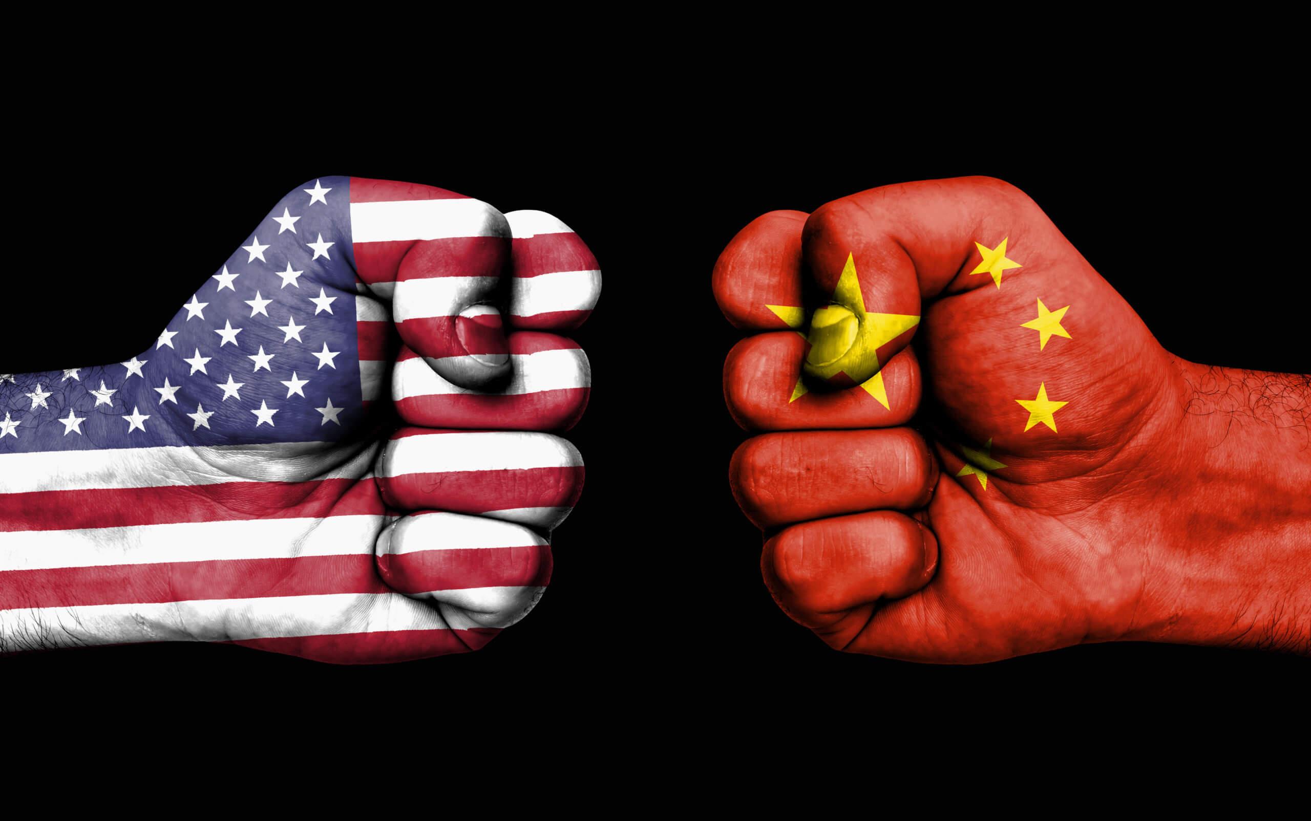 zwei fäuste, die auf einander zukommen, eine gefärbt mit der flagge der usa, die andere mit der flagge von china