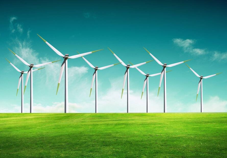 weiße windräder auf einer grünen wiese vor einem blauen himmel mit wolken
