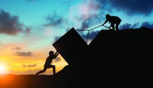 zwei silouhetten von menschen, die einen quadratischen Stein einen Hügel mi einem Seil hochziehen